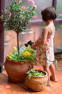Little girl watering the plants on the terrace