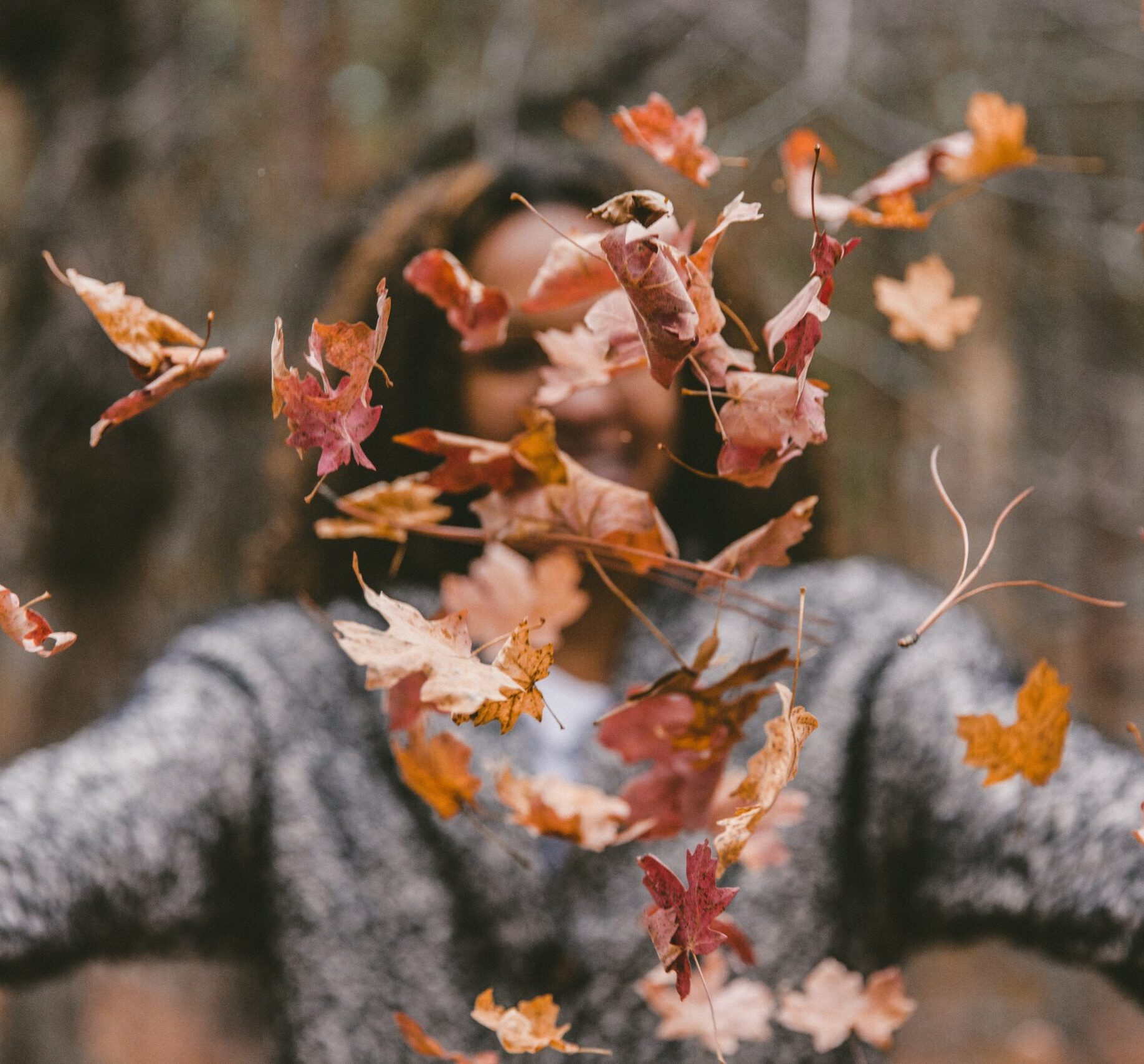 happy person throwing fall leaves in air